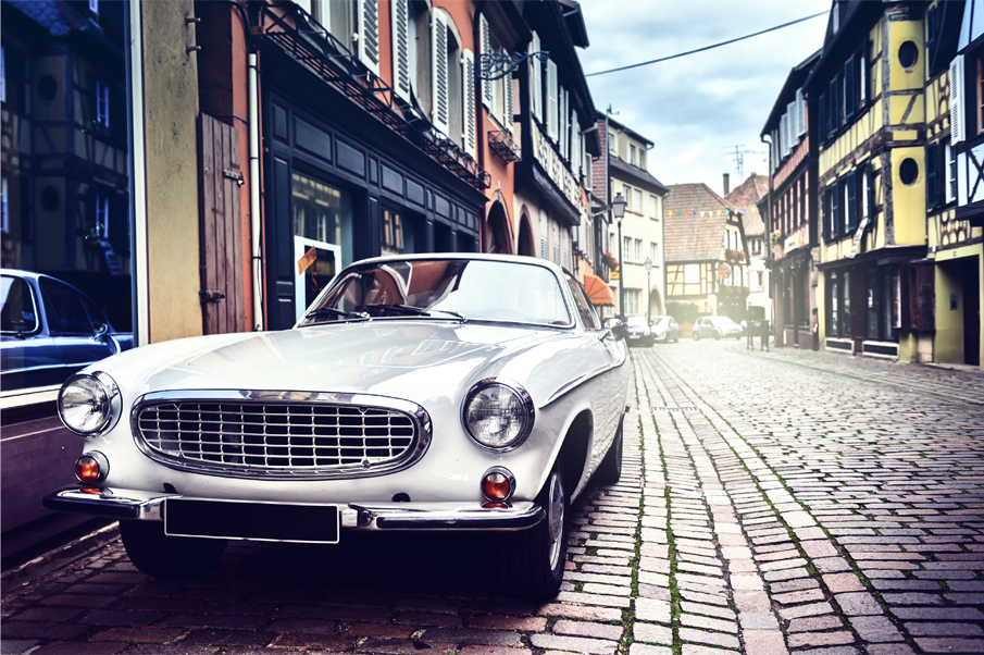 White classic car parked in a cobbled street